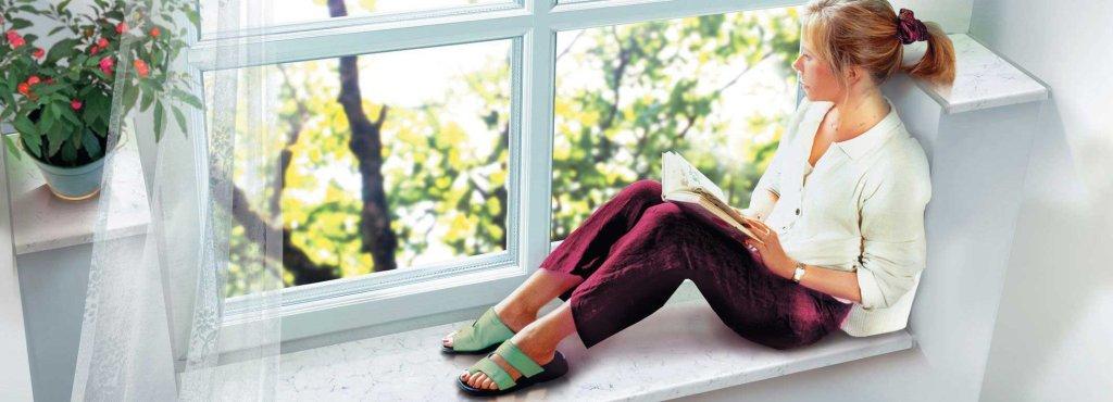 Дівчина з книгою на підвіконні
